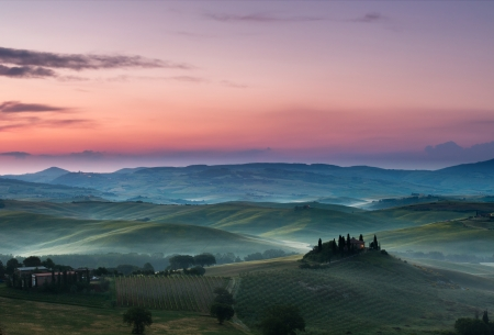 White fog and purple clouds on a beautiful morning in the Tuscan hills with view on Belvedere in San Quirico d'Orcia