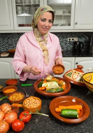 immigrants: Moroccan immigrant woman in modern European kitchen preparing traditional tajine dish for Ramadan nights