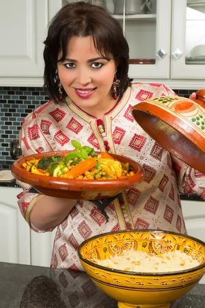 moroccan cuisine: Beautiful Moroccan immigrant woman in Europe presenting her tajine dish during Ramadan in her modern kitchen