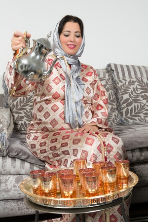 sugar veil: Moroccan immigrant woman in Europe pouring tea for her guests Stock Photo