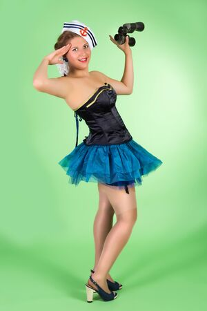 Saluting pin up girl in sailor costume photo