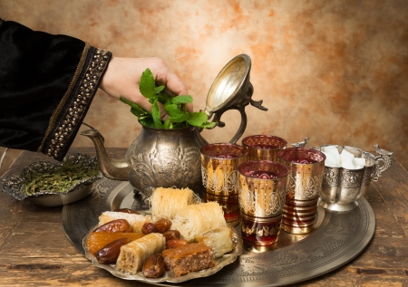 Female hand adding mint leaves to a tray with dates, cookies and tea the moroccan style