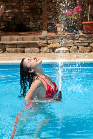 Summer fun of a young woman playing with a water hose in the swimming-pool photo