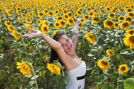 Singing young woman in a yellow bulgarian sunflower field photo