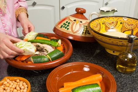 Hands of a woman preparing couscous and a traditional Moroccan tajine during Ramadan nights (Moroccan immigrant woman in modern European kitchen) photo