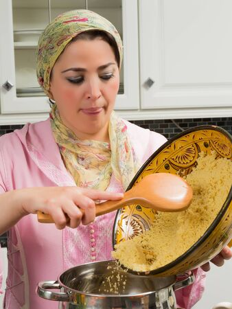 moroccan cuisine: Couscous being prepared by a Moroccan immigrant woman in her modern European kitchen
