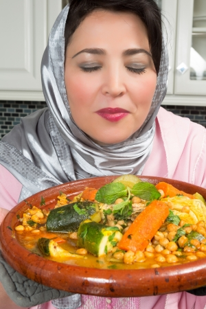 Moroccan immigrant woman in Europe presenting her tajine dish during Ramadan in her modern kitchen photo