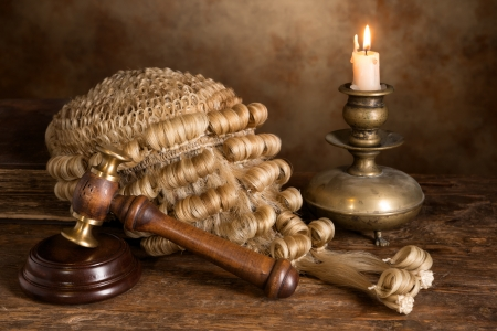 Still life with candle, judges antique wig and gavel