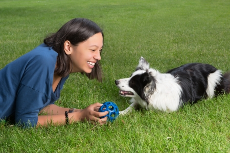Smiling woman playing fetch the ball with her border collie dog