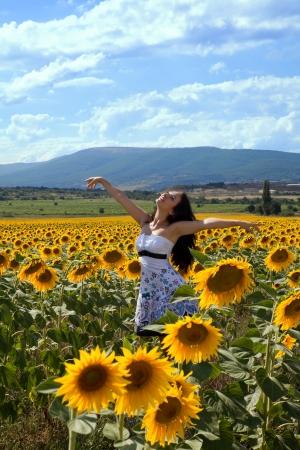 Dancing young woman having fun in a Bulgarian sunflower field photo