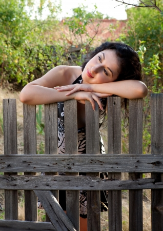 Pretty lonely woman leaning against a wooden fence photo