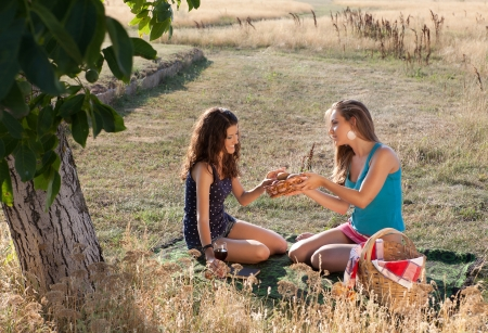Young girls sharing bread during a picnic in golden evening light photo