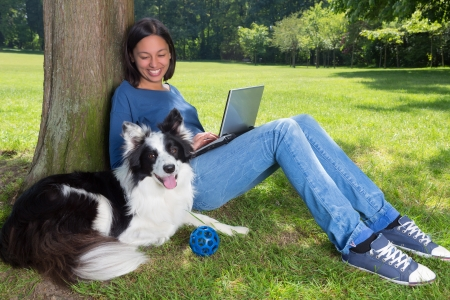 laptop outside: Girl working on her laptop in the park and her dog waiting to play with a ball