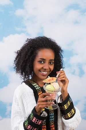 Smiling African girl with Ethiopian costume eating icecream photo