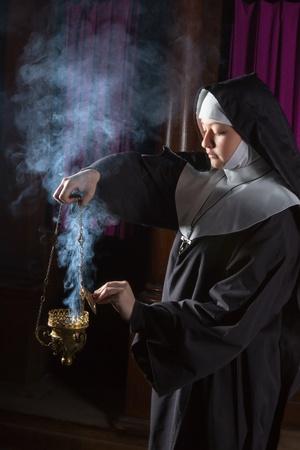 incienso: Monja joven que se prepara un quemador de incienso para la masa