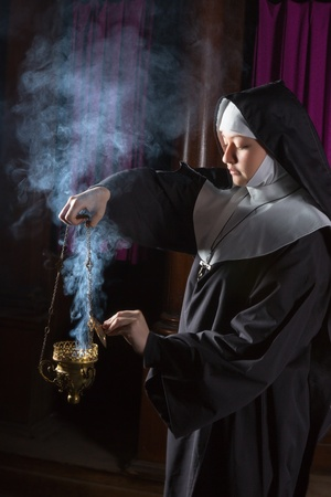 nun: Young nun preparing an incense burner for mass Stock Photo