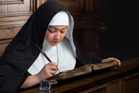 nun: Vintage scene of a young nun writing in an ancient book Stock Photo