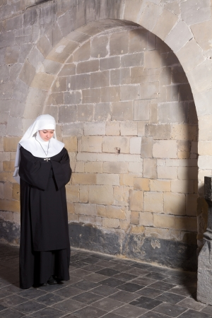 carmelite nun: Young novice standing near the old walls of a medieval church