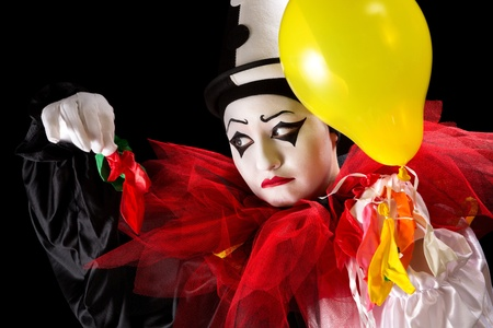 Sad Pierrot clown holding the left-overs of his balloons photo