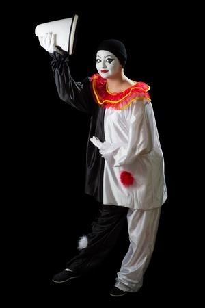 Mime de Pierrot aislado en negro saludo con su sombrero