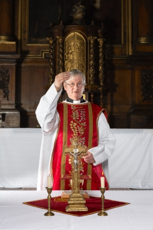 catholic mass: Priest blessing the community during catholic mass in a medieval church with 17th century interior Stock Photo