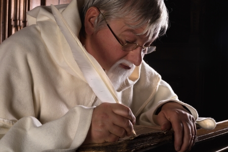 convent: Monk writing in an ancient book with a feather quill