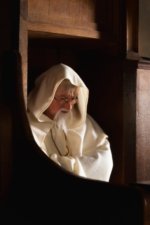 franciscan: Hooded monk sitting in a choir seat of a medieval church