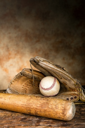 Baseball bat with ball and old weathered glove Stock Photo