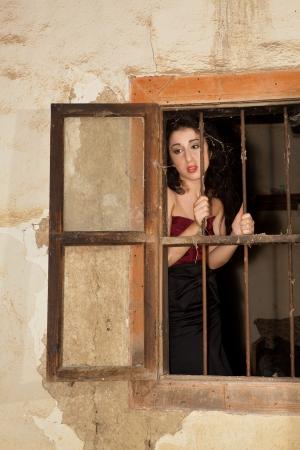 melancholic: Melancholic woman behind bars of a derelict building Stock Photo