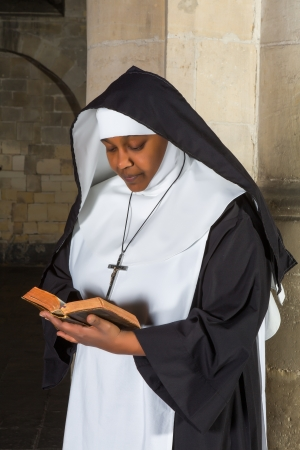 african worship: Mature nun reading the bible in a medieval church Stock Photo