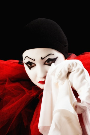Mime actor dressed as Pierrot crying with a hanky photo