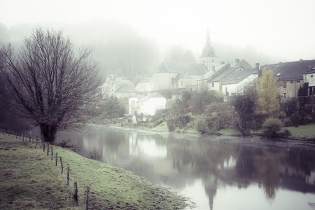 Desaturated image of morning mist hanging over the Semois river at Chassepierre village in the Gaume region of the Belgian Ardennes photo