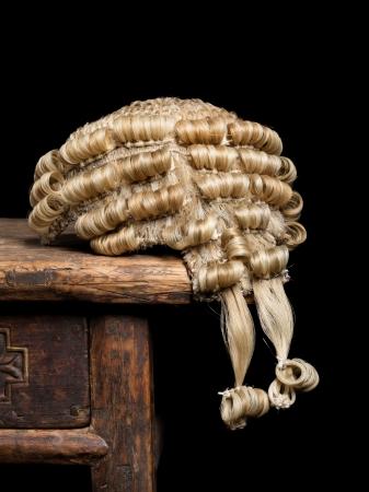 Closeup of a genuine judges wig on an antique wooden desk