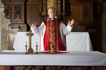 Christian priest blessing the hosts and chalice in a 17th century church interior Stock Photo