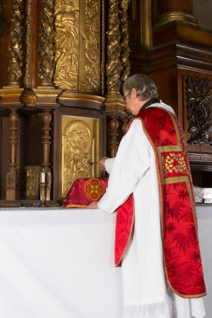 vestment: After the communion, a catholic priest returns the chalice into the 17th century tabernacle of a medieval church with baroque interior Stock Photo
