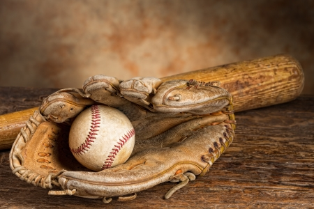 Old baseball bat with ball and weathered glove photo