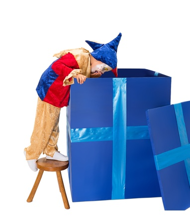 Funny jester clown girl looking deep into a big blue surprise box photo