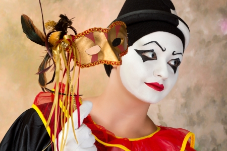 painted face mask: Young female pierrot holding a leather venice mask