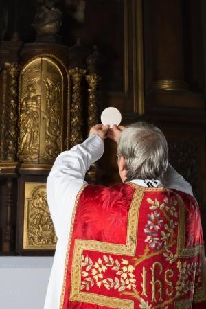 sacerdote: Consagración durante la misa católica antigua en el interior de una iglesia del siglo 17
