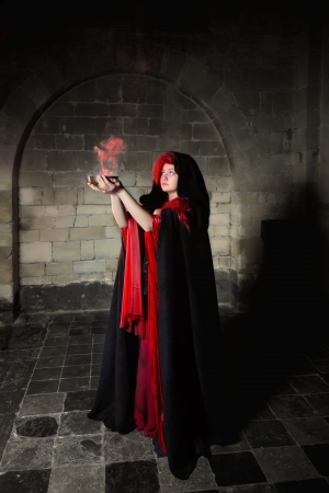 Red sorceress with black cape and red smoke photo