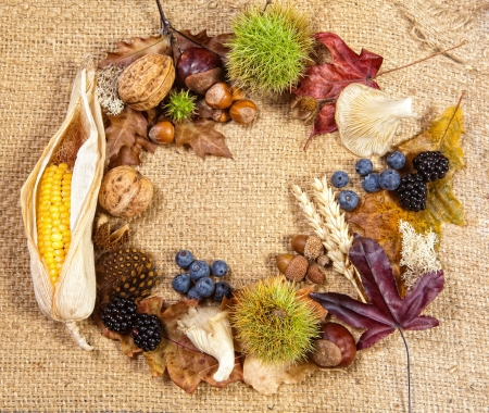 Circular composite of autumn fruits leaves and nuts on jute photo