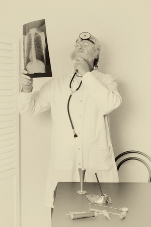 Old faded effect on a vintage doctor examining an x-ray photo
