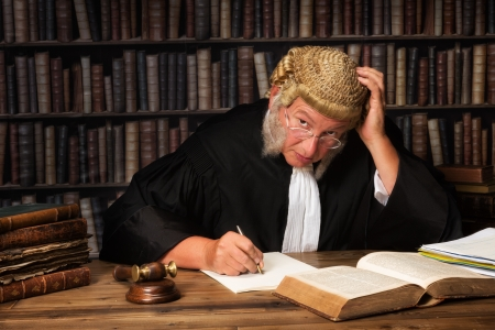 Mature judge with authentic court wig and gavel in court