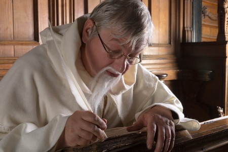 franciscan: Monk with beard writing with a feather in an old book
