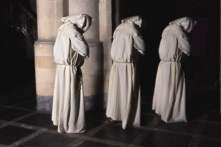 christian halloween: Hooded monks walking in a dark medieval church