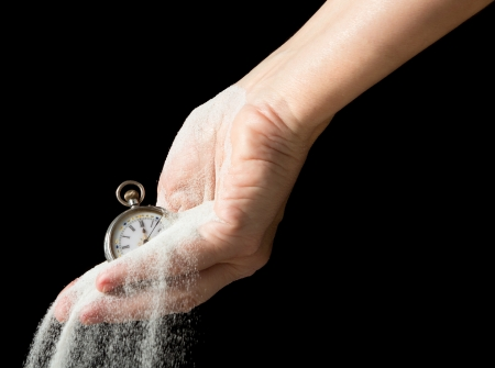 Sand flowing between fingers of a hand holding an antique pocket watch 版權商用圖片