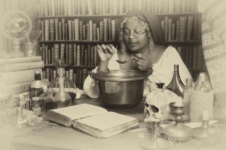 Vintage alchemist adding herbs to a smoking kettle photo