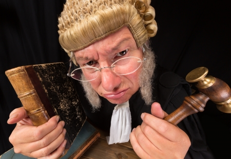 Grumpy old judge in extreme wide angle closeup with hammer and wig Stock Photo