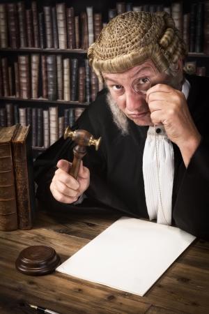 martillo juez: Juez divertido que mira a trav�s de un antiguo mon�culo Foto de archivo