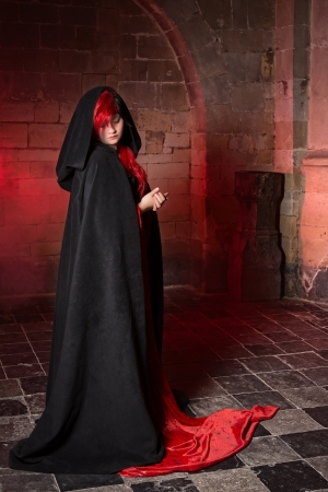 Gothic witch woman standing in a medieval castle photo